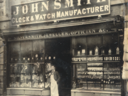 The shop in Queen Street in 1888. It shows Frank Smith proudly standing in front of the retail outlet for the clocks & watches both made by the firm and bought in from UK and foreign suppliers. This was later moved to a small shop in the Market Place.